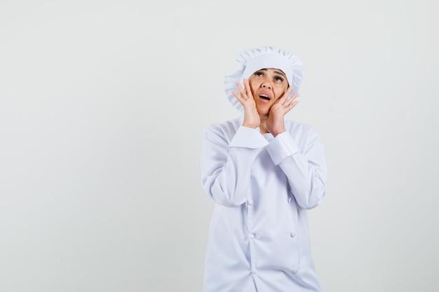 Vrouwelijke chef-kok die handen dichtbij mond in wit uniform houdt en bezorgd kijkt Gratis Foto