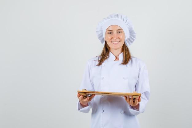 Vrouwelijke chef-kok die houten dienblad in wit uniform houdt en vrolijk kijkt. vooraanzicht. Gratis Foto