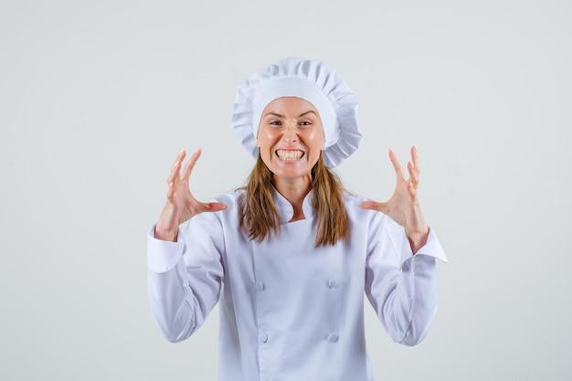 Vrouwelijke chef-kok die tanden op elkaar klemt en handen met woede opheft in wit uniform vooraanzicht. Gratis Foto