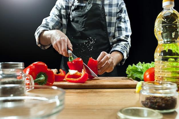 Vrouwelijke chef-kok die verse groenten snijdt Gratis Foto