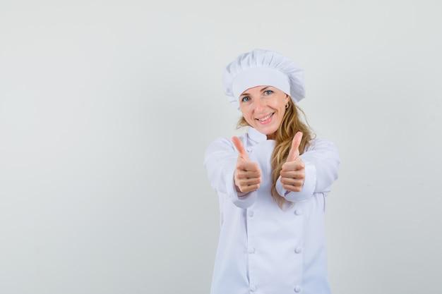 Vrouwelijke chef-kok dubbele duimen opdagen in wit uniform en vrolijk kijken Gratis Foto