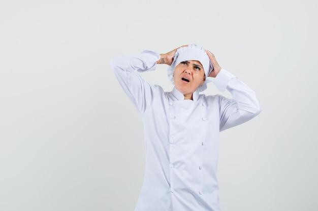 Vrouwelijke chef-kok hand in hand op het hoofd in wit uniform en op zoek weemoedig Gratis Foto