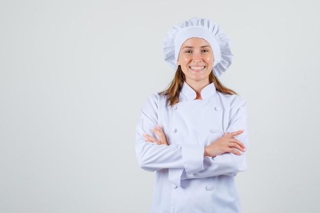 Vrouwelijke chef-kok in wit uniform staande met gekruiste armen en vrolijk kijken Gratis Foto