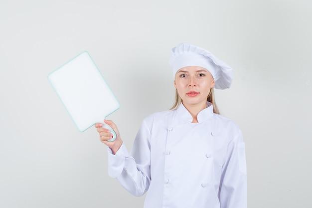 Vrouwelijke chef-kok in witte uniforme snijplank houden en glimlachen Gratis Foto