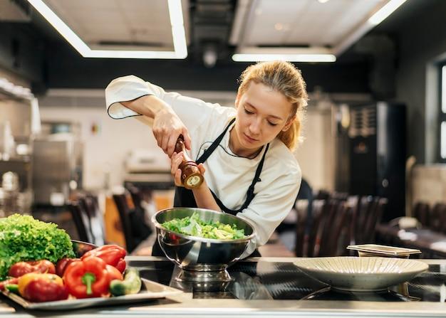 Vrouwelijke chef-kok kruiden salade in de keuken Premium Foto
