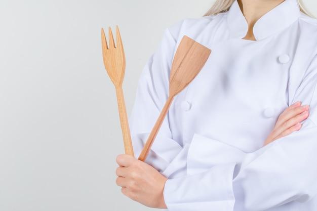 Vrouwelijke chef-kok met houten vork en spatel in wit uniform Gratis Foto