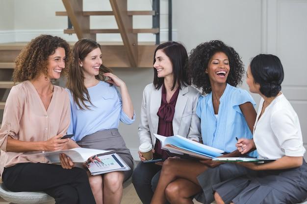 Vrouwelijke collega's die met elkaar interactie aangaan Premium Foto
