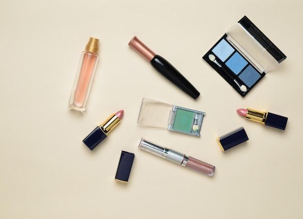 Vrouwelijke cosmetica voor make-up lay-out. cosmetische schaduwen, make-up kwast, oogschaduw lippenstift, parfumflesje. plat lag, bovenaanzicht. kopieer ruimte. Premium Foto