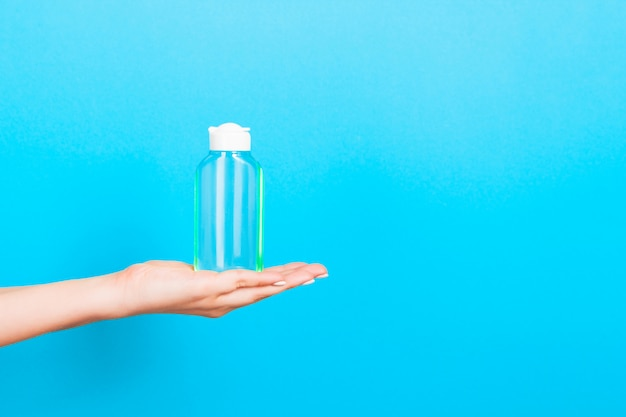 Vrouwelijke de roomfles van de handholding geïsoleerde lotion. het meisje geeft buiscosmetischee producten op blauw Premium Foto