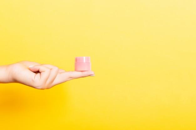 Vrouwelijke de roomfles van de handholding geïsoleerde lotion. het meisje geeft kruikcosmetischee producten op geel Premium Foto