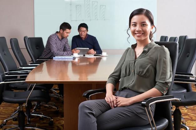 Vrouwelijke directeur die het bureau met haar collega's zit die bij digitaal stootkussen op de achtergrond werken Gratis Foto