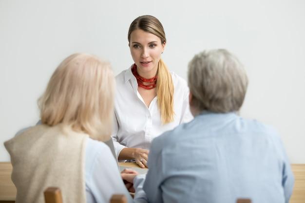 Vrouwelijke financiële adviseur die raadplegen hoger oud paar op vergadering spreekt Gratis Foto