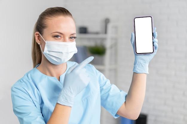 Vrouwelijke fysiotherapeut met medisch masker houden en wijzen op smartphone Gratis Foto