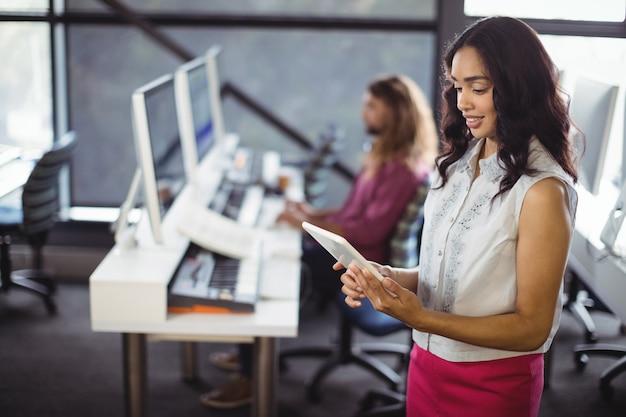 Vrouwelijke geluidstechnicus in studio met behulp van digitale tablet Gratis Foto