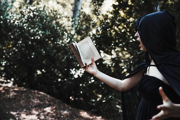Vrouwelijke goochelaar lezen spreuk in het kreupelhout Gratis Foto