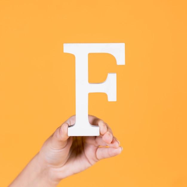 Vrouwelijke hand die de hoofdletter f houdt Gratis Foto