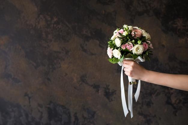 Vrouwelijke hand die een huwelijksboeket op dark houdt Premium Foto