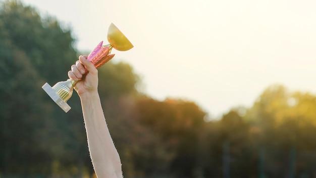 Vrouwelijke hand die een trofee opheft Gratis Foto