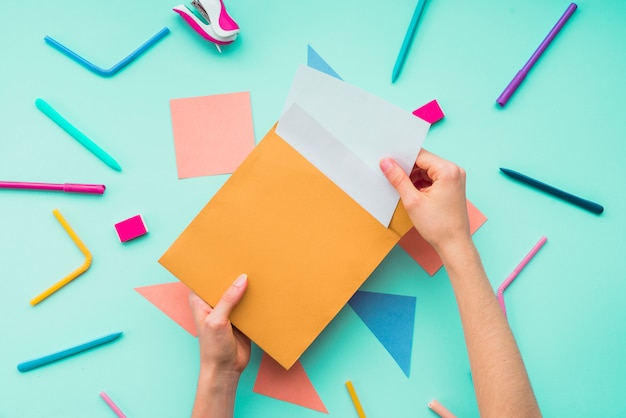 Vrouwelijke hand die kaart verwijdert uit envelop over de kantoorbehoeftentoebehoren Gratis Foto