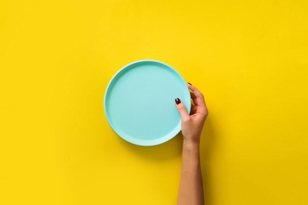 Vrouwelijke hand die lege blauwe plaat op gele achtergrond met exemplaarruimte houdt. Premium Foto