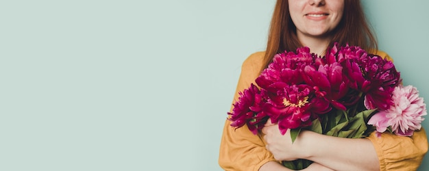 Vrouwelijke hand die mooi boeket met geurige pioenen houdt Premium Foto