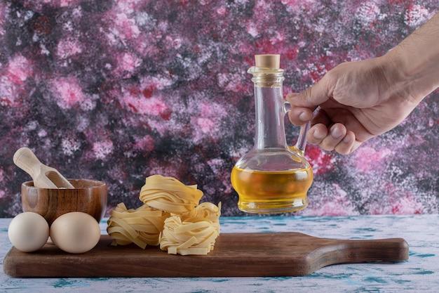 Vrouwelijke hand die oliefles neemt van houten plank. Gratis Foto