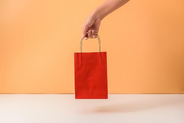 Vrouwelijke hand die rode papaer het winkelen zakken houdt Premium Foto