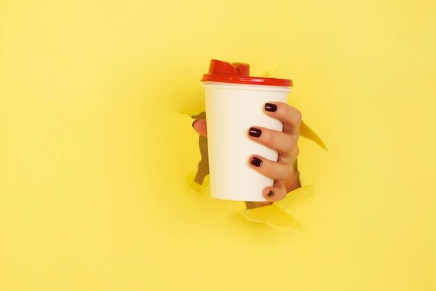 Vrouwelijke hand die witboekmok op gele achtergrond houdt. Premium Foto