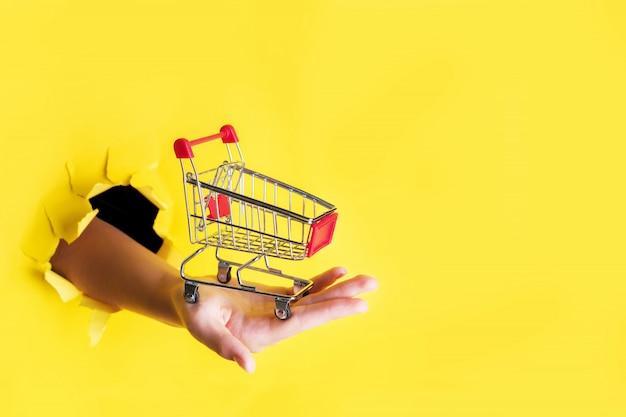 Vrouwelijke hand houdt door een gat een mini boodschappen kar op een geel papier. verkoop concept Premium Foto