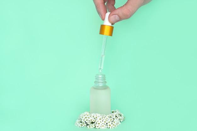 Vrouwelijke hand houdt een druppelaar uit een fles met olie. glazen container voor een cosmetisch product voor vrouwen met kleine witte bloemen op een groene achtergrond Premium Foto