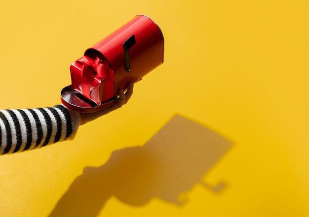 Vrouwelijke hand houdt gfit-box in brievenbus op gele ondergrond Premium Foto
