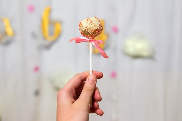 Vrouwelijke hand houdt pop cakes op pastel achtergrond. witte chocolade cake pop versierd met kleurrijke hagelslag. partij concept. Premium Foto