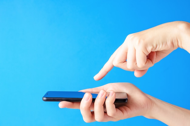 Vrouwelijke hand houdt smartphone op blauwe achtergrond. de mobiele vertoning van de vrouwenaanraking met vinger Premium Foto
