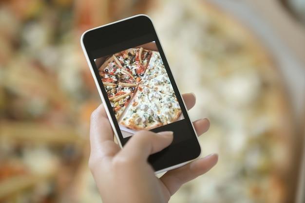Vrouwelijke hand maken een foto van pizza Gratis Foto