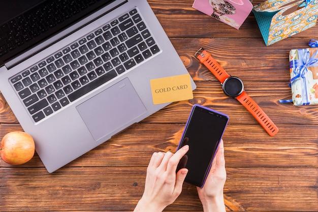 Vrouwelijke hand met behulp van mobiele telefoon over houten oppervlak Gratis Foto