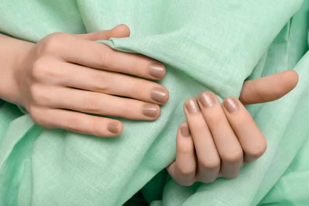 Vrouwelijke hand met beige glitter nagel ontwerp Gratis Foto