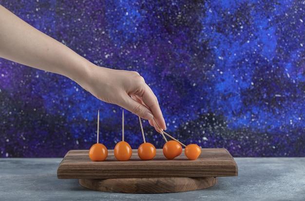 Vrouwelijke hand met cherrytomaat van houten bord. Gratis Foto