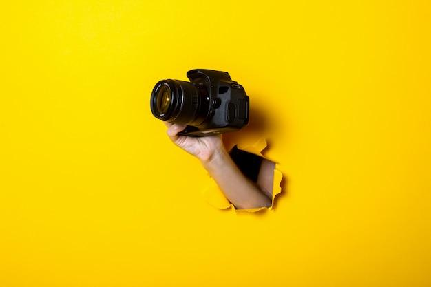 Vrouwelijke hand met een camera op een heldere gele achtergrond Premium Foto