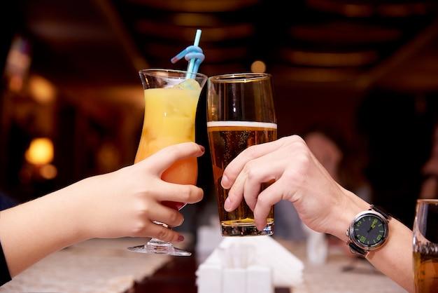 Vrouwelijke hand met een cocktail en een mannelijke hand met bierclose-up. Premium Foto