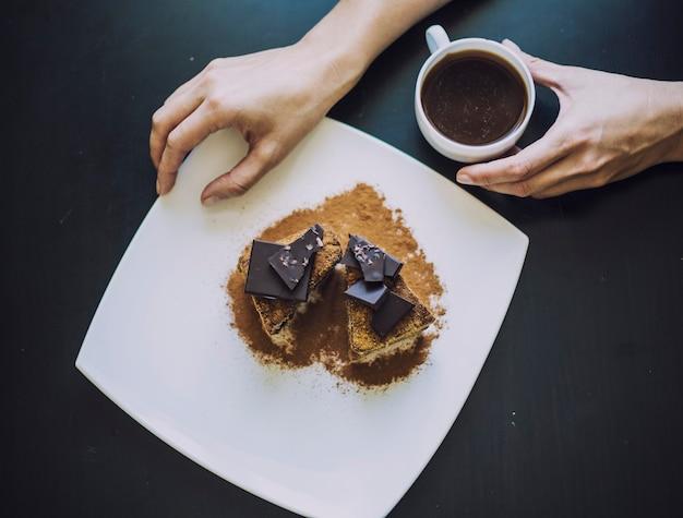 Vrouwelijke hand met een kopje koffie en een mooie close-up van de chocoladetaart op tafel Premium Foto