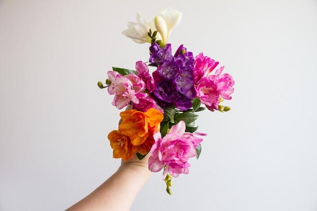 Vrouwelijke hand met een prachtig kleurrijk bloemboeket Gratis Foto