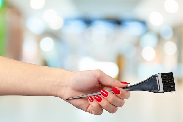 Vrouwelijke hand met kapper kam in cosmetische winkel Premium Foto