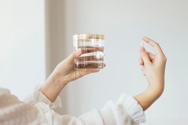Vrouwelijke hand met omega 3 visoliesupplementcapsule en glas water Premium Foto