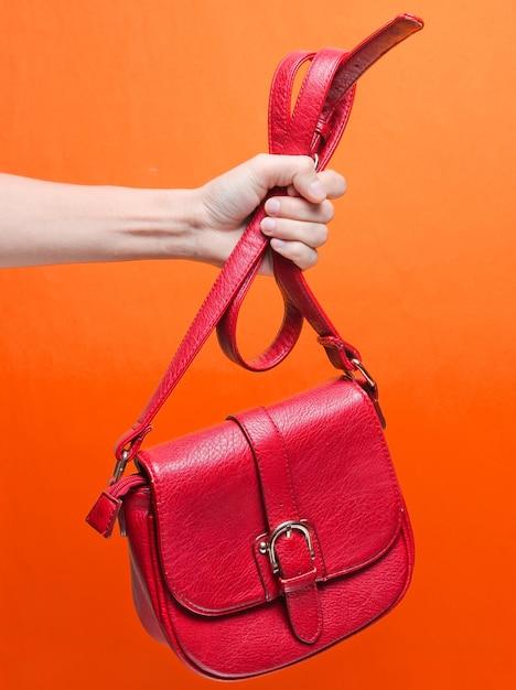 Vrouwelijke hand met rode leerzak bij de riem Premium Foto
