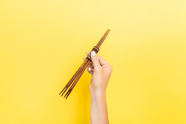 Vrouwelijke hand met stokjes. sushiconcept met lege ruimte Premium Foto