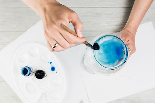 Vrouwelijke hand schilderij op glazen pot met verf penseel over houten bureau Gratis Foto