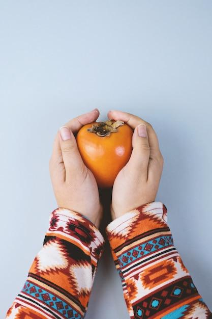 Vrouwelijke hand schuilt rijpe persimmon Premium Foto