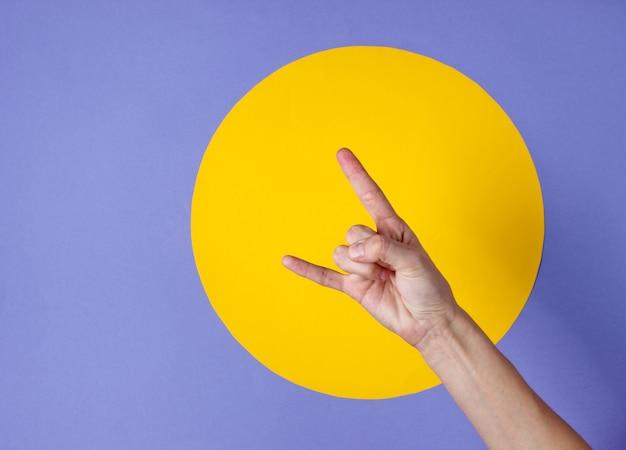 Vrouwelijke hand toont rock gebaar op paars met gele cirkel Premium Foto