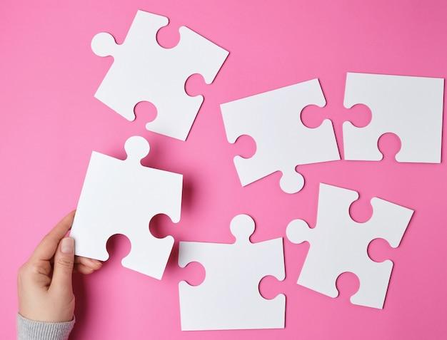 Vrouwelijke hand zet witte grote puzzels op roze Premium Foto
