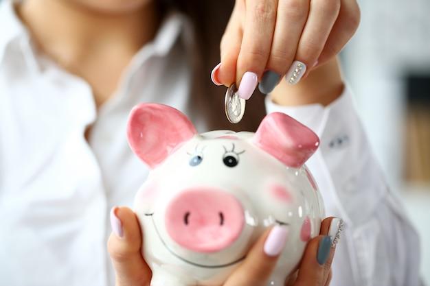 Vrouwelijke hand zet zilveren kwart in spaarpot Premium Foto